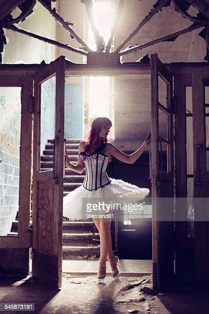 Germany, Brandenburg, Beelitz, woman with red hair and ballerina dress standing in destroyed old house at backlight