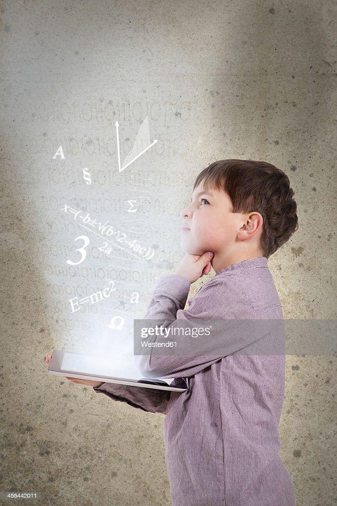 Germany, Brandenburg, Boy thinking with digital tablet