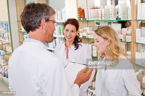 Germany, Brandenburg, Man and women having team meeting in pharmacy