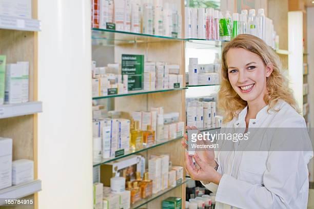 Germany, Brandenburg, Pharmacist showing product, smiling, portrait