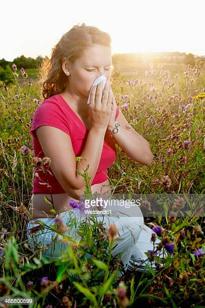 Germany, Brandenburg, young pregnant woman with hay fever kneeling in a flower meadow
