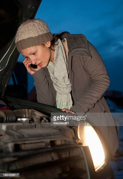 Germany, Brandenburg, Young woman with car break down at night, talking on mobile phone