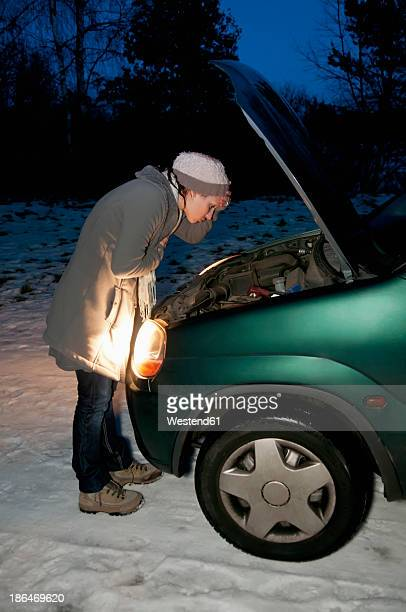 Germany, Brandenburg, Young woman with car breaks down at night