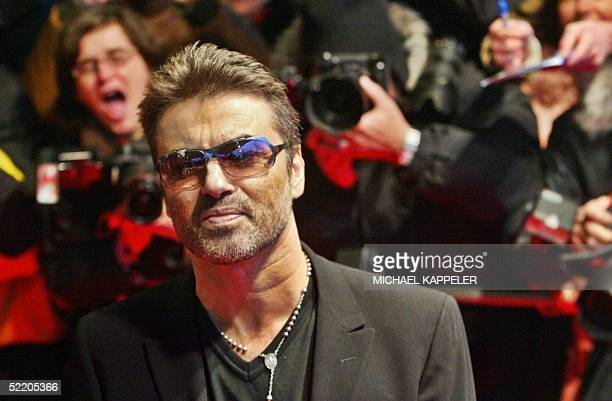 British pop star George Michael poses as he walks over the red carpet prior the screening of 'George Michael A Different Story' at the Berlin Film...
