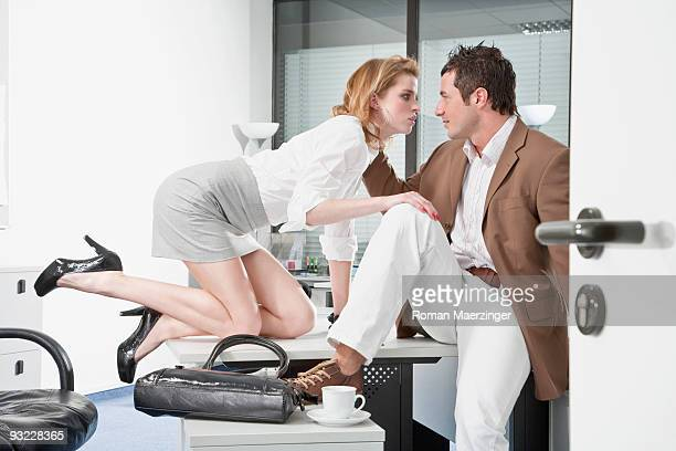 Germany, Businessman and woman flirting in office