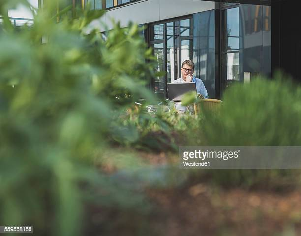 Germany, Businessman sitting in cafeteria working at laptop