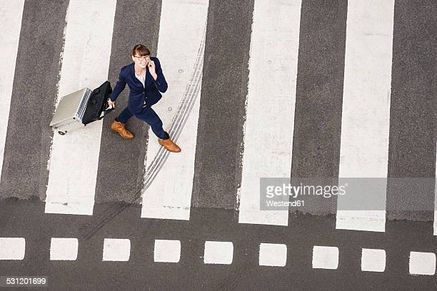 Germany, businesswoman with rolling suitcase walking on zebra crossing, view from above