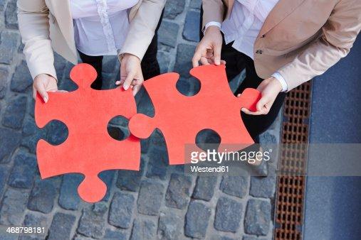 Germany, Businesswomen holding jigsaw pieces