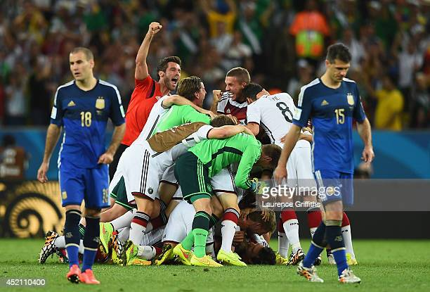 Germany celebrate after defeating Argentina in extra time 10 as Rodrigo Palacio and Martin Demichelis of Argentina look on during the 2014 FIFA World...