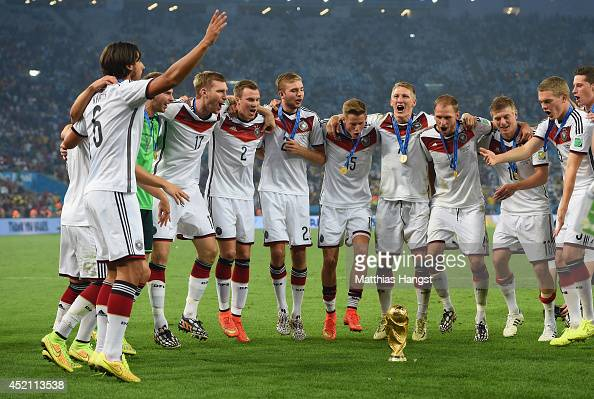 Germany celebrate around the World Cup trophy after defeating Argentina 10 in extra time during the 2014 FIFA World Cup Brazil Final match between...