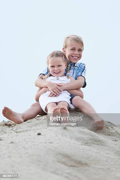 Germany, Children (4-7) sitting on sand dune, smiling, portrait