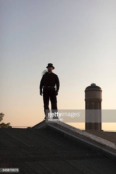 Germany, chimney sweep standing on rooftop at twilight