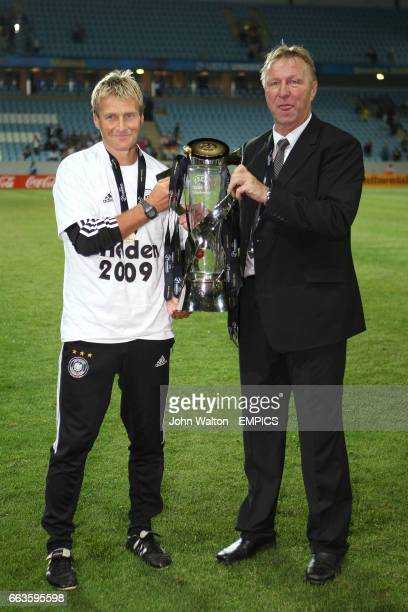 Germany coach Horst Hrubesch and assistant Thomas Noerenberg celebrate with the trophy after winning the UEFA European U21 Championship 2009 Final
