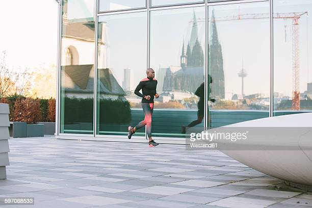 Germany, Cologne, athlete running at glass front of a building with reflection of Cologne Cathedral