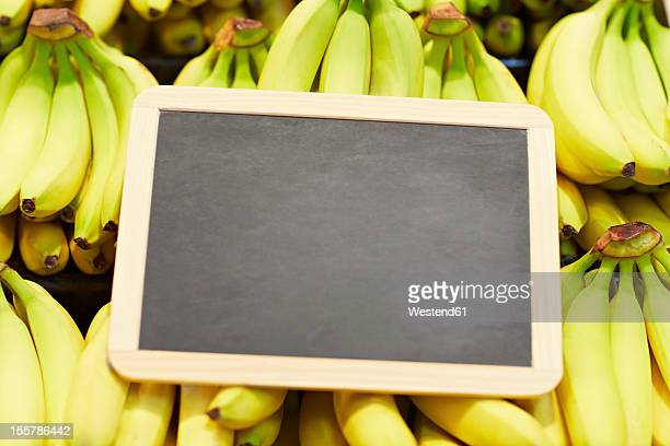 Germany, Cologne, Bananas with blackboard in supermarket, close up