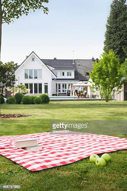 Germany, Cologne, Booksand apples on blanket in garden