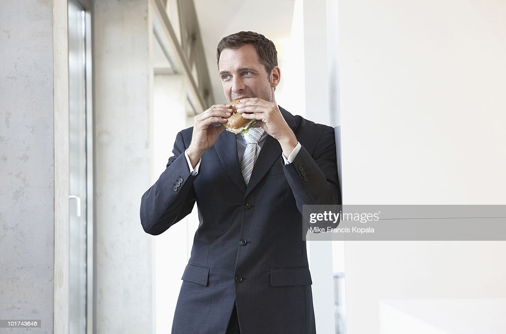 Germany, Cologne, Businessman eating sandwich, portrait : Stock Photo