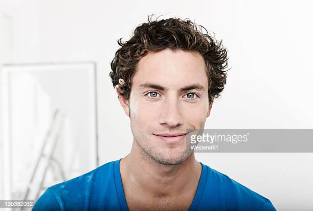 Germany, Cologne, Close up of young man with pencil behind ear in renovating apartment, portrait, smiling