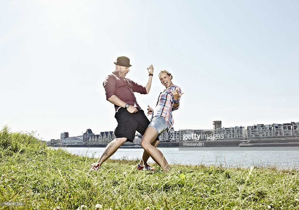 Germany, Cologne, Couple playing air guitar