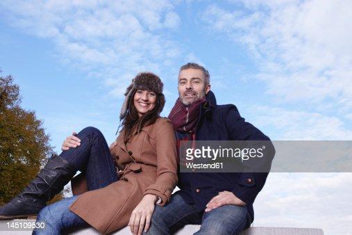 Germany, Cologne, Couple sitting on bridge, smiling, portrait