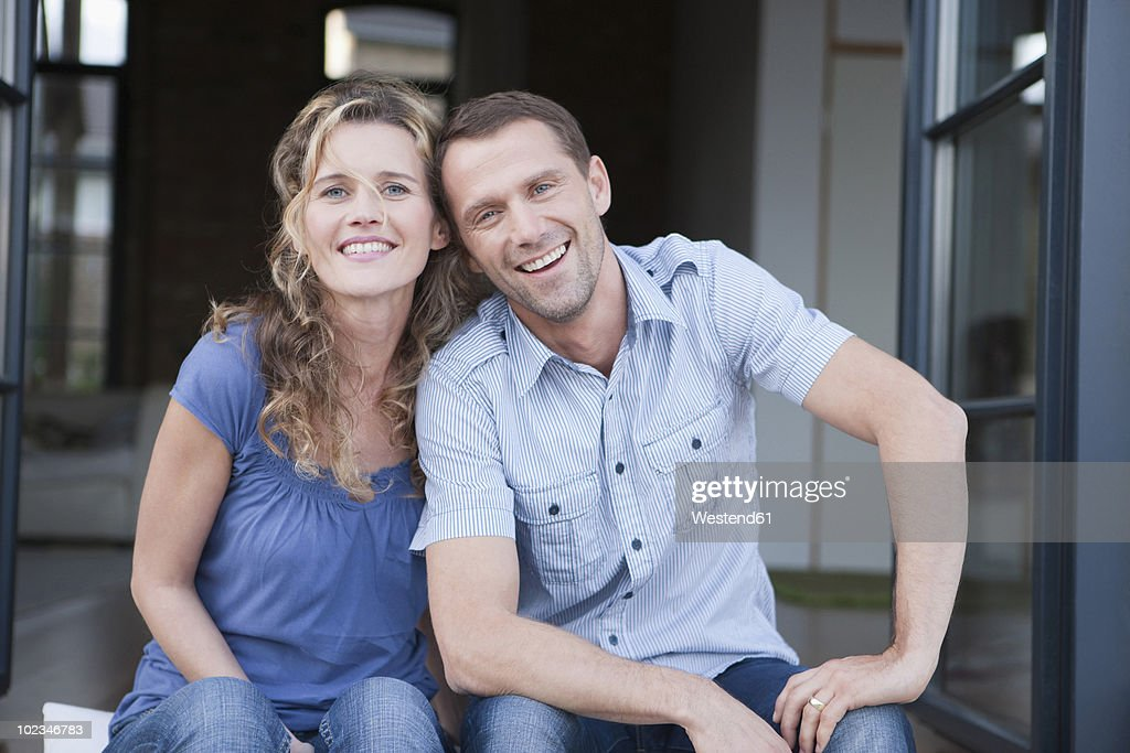 Germany, Cologne, Couple sitting on terrace, smiling, portrait