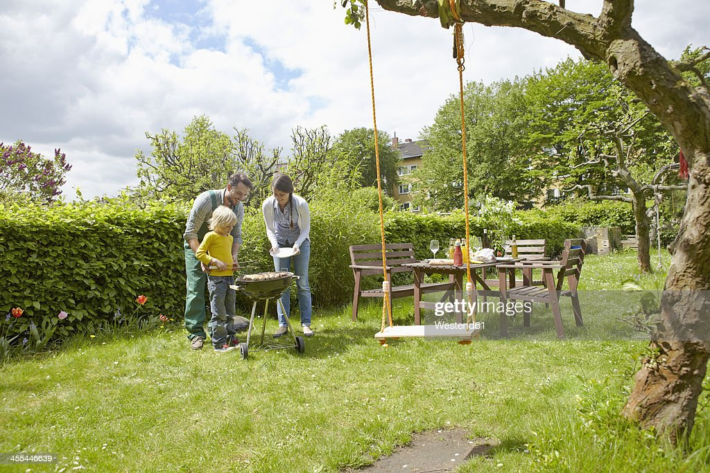 Germany, Cologne, Family having barbecue in garden