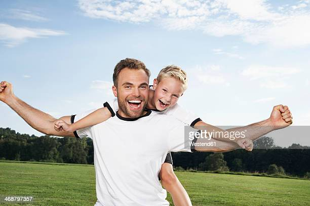Germany, Cologne, Father and son cheering in football outfit