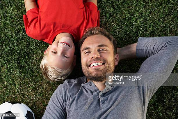 Germany, Cologne, Father and son lying in meadow