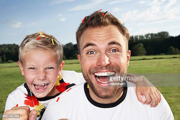 Germany, Cologne, Father and son supporting their soccer team