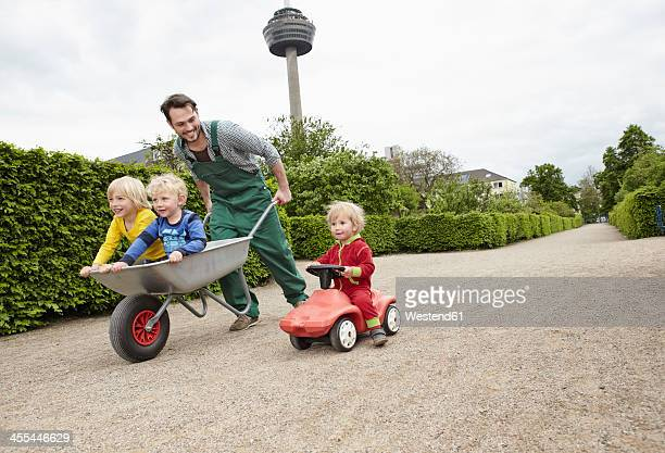 Germany, Cologne, Father carrying daughter and son in wheelbarrow, smiling