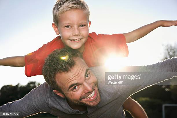 Germany, Cologne, Father carrying son, pretending to fly