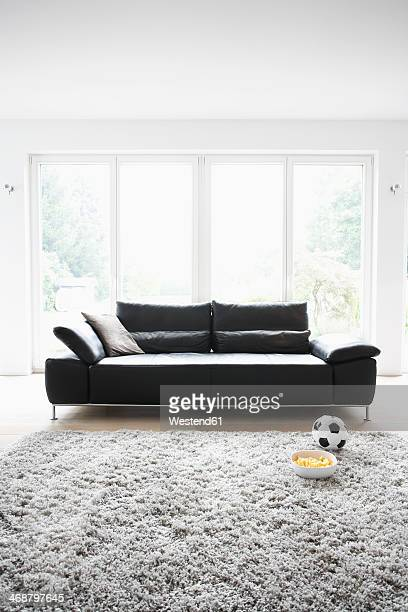 Germany, Cologne, Football and chips in front of couch