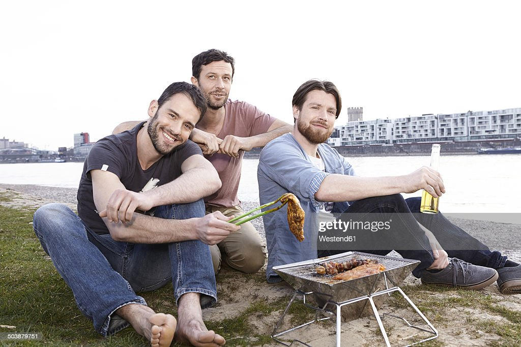 Germany, Cologne, Friends having barbecue at the riverside