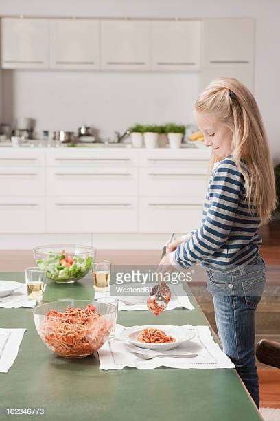 Germany, Cologne, Girl (6-7) serving spaghetti, side view