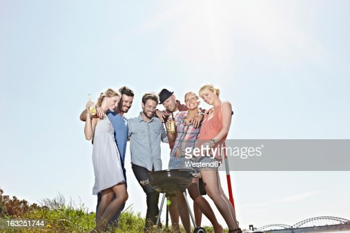 Germany, Cologne, Group of people gathered around barbecue : Stock Photo
