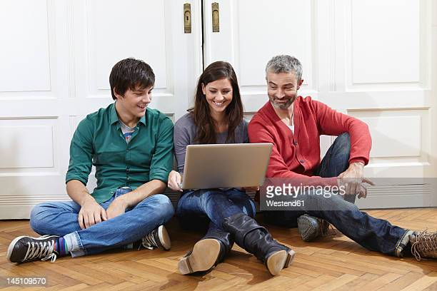 Germany, Cologne, Man and woman using laptop, smiling