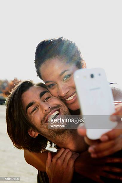 Germany, Cologne, Man giving piggy back ride to woman, smiling
