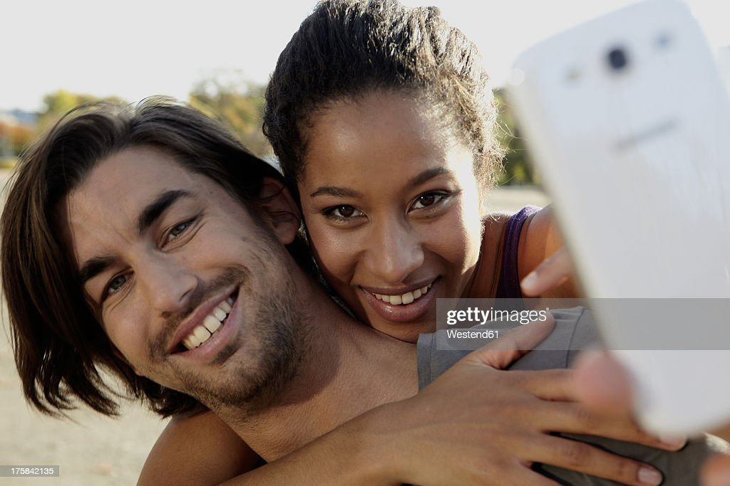 Germany, Cologne, Man giving piggy back ride to woman, smiling : Stock Photo