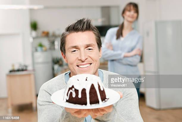 Germany, Cologne, Man holding cake in domestic kitchen