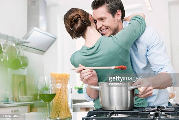 Germany, Cologne, Man preparing sauce, woman embracing man