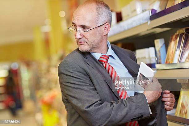 Germany, Cologne, Mature man shoplifting in supermarket
