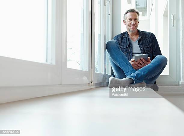 Germany, Cologne, Mature man sitting at window using digital tablet