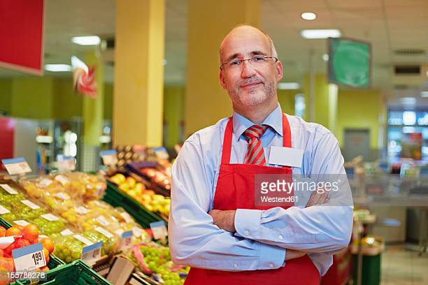 Germany, Cologne, Mature man standing in supermarket, smiling, portrait