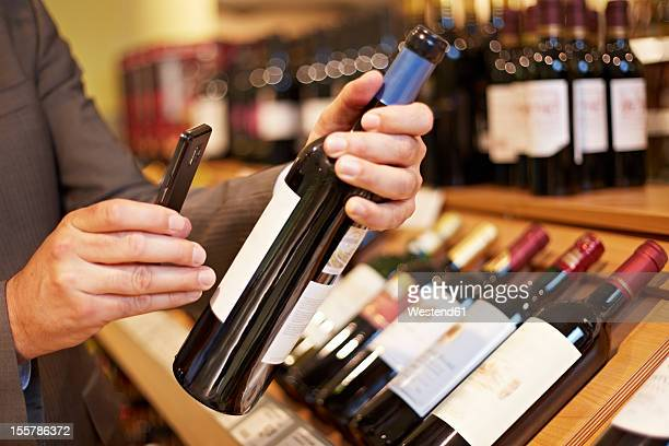 Germany, Cologne, Mature man taking picture of wine bottle in supermarket