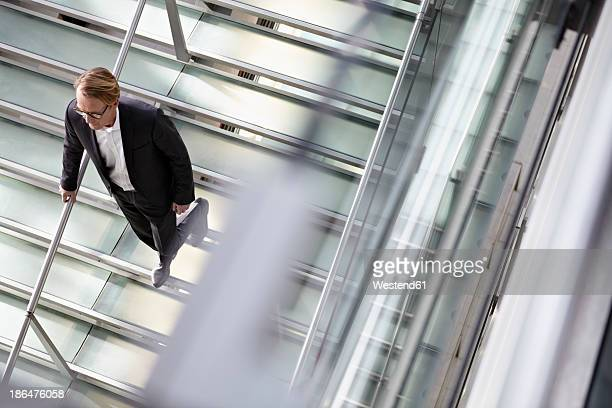 Germany, Cologne, Mature man walking down stairs