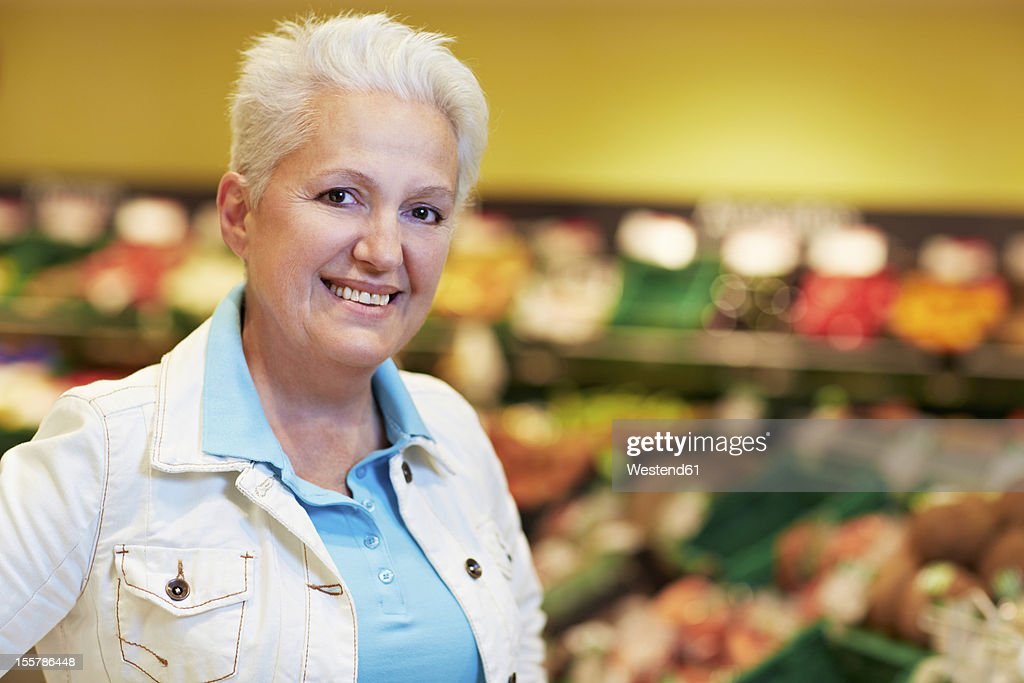 Germany, Cologne, Mature woman in supermarket, smiling, portrait : Stock Photo