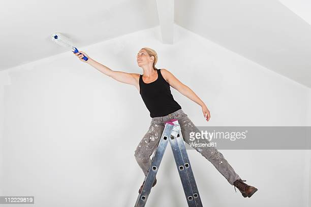Germany, Cologne, Mature woman on step ladder and painting gable roof of living room
