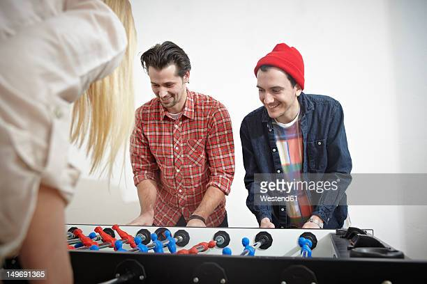 Germany, Cologne, Men and woman playing table soccer, smiling