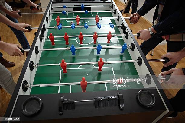 Germany, Cologne, Men and women playing table soccer