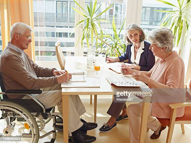 Germany, Cologne, Men on wheelchair with women sitting in nursing home
